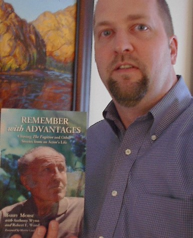 "Anthony Wynn, holding the book ""Remember with Advantages""."