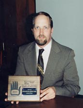 Anthony Wynn holding the Award of Excellence